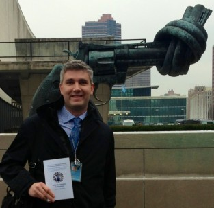 "Chad is holding the 2013 Civil Society Declaration in front of ""Non-Violence"" (also known as ""The Knotted Gun""), which is a pro-peace sculpture by Swedish artist Carl Fredrik Reuterswärd designed in late 1980 and inspired by the shooting death of his friend, John Lennon. It was given to the UN by the government of Luxembourg in 1988."