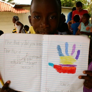 Jamaican Student Showing his Work in his Notebook