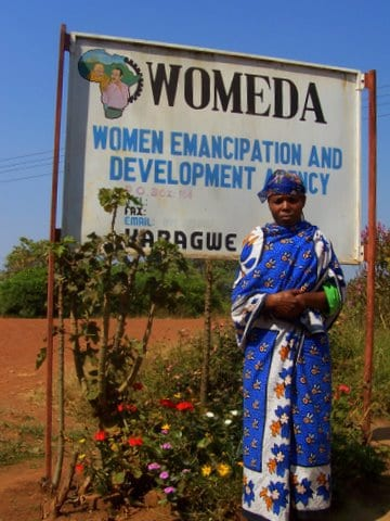 Local woman standing in front of the sign for WOMEDA